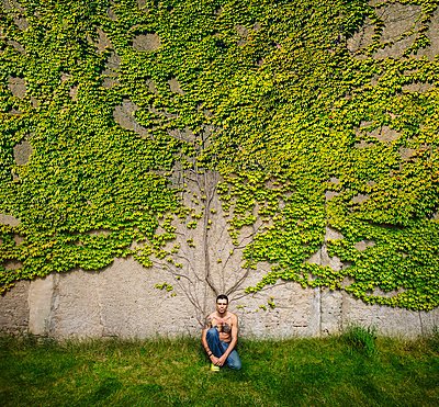 Portrait man with tattooed chest sitting at wall overgrown with ivy - p301m2075525 by Sven Hagolani