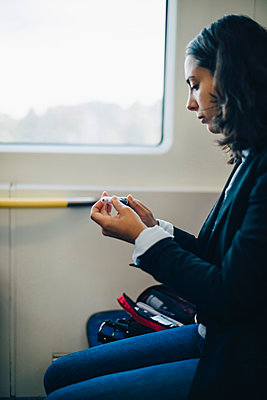 Woman looking at injection pen while sitting by window in train - p426m1537162 by Maskot