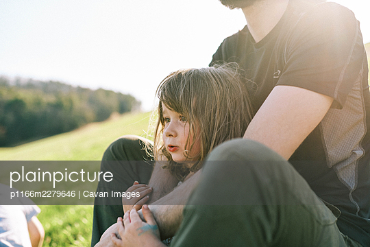 Little girl leaning against her father while resting on a hill in sun - p1166m2279646 by Cavan Images