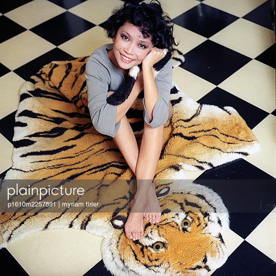 A woman sits on a fake tiger carpet  - p1610m2257891 by myriam tirler