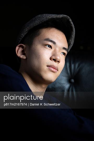 Young Asian man with cap, portrait - p817m2167974 by Daniel K Schweitzer
