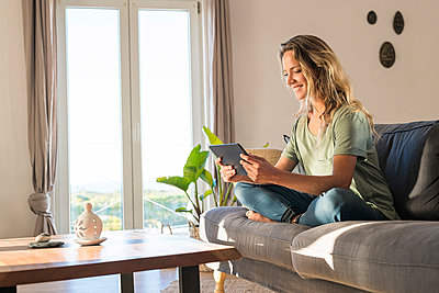 Happy woman realxing on couch at home using tablet - p300m2104422 von Steve Brookland