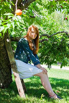 Girl sitting under a fruit tree - p756m740346 by Bénédicte Lassalle