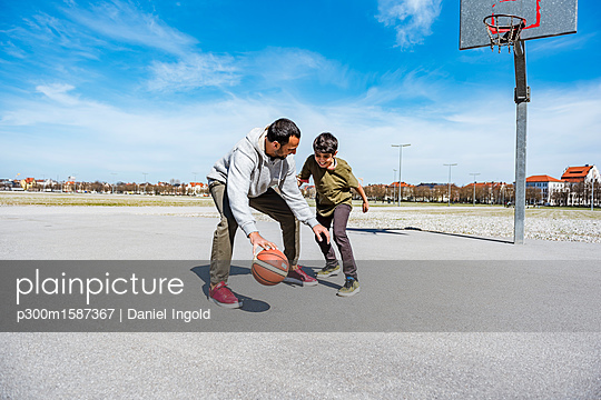 Father and son playing basketball on court outdoors - p300m1587367 von Daniel Ingold