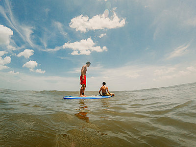 Shirtless brothers paddleboarding on sea against sky - p1166m2011179 by Cavan Images