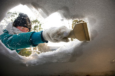 Woman clearing snow of windshield - p1231m1043132 by Iris Loonen