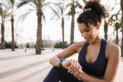 Female athlete checking time on wristwatch - p300m2276710 by Xavier Lorenzo