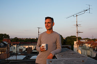 Man holding coffee mug on roof - p341m2008667 by Mikesch