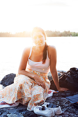 Young woman sitting in front of a lake in Dalarna, Sweden - p352m2039905 by Anna Larsson