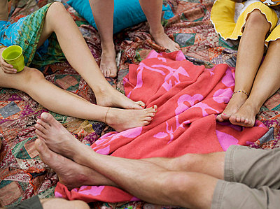 Four pair of bare feet on blankets - p4292760f by Ricky Molloy