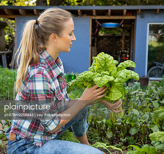 Blonde woman in her garden - p1678m2258843 by vey Fotoproduction