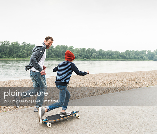 Happy father running next to son on skateboard at the riverside - p300m2004357 von Uwe Umstätter