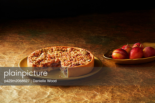 Still life with plum and almond tart on gold plate, christmas dessert - p429m2068627 by Danielle Wood