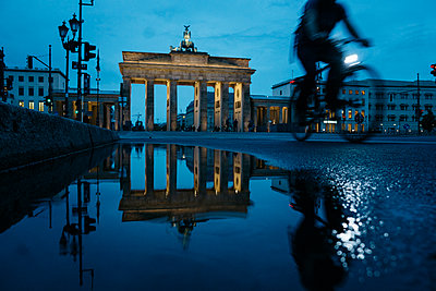 Germany, Berlin, view to  Brandenburg Gate reflecting in puddle by night - p300m1469880 by Michael Zwahlen