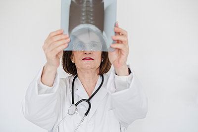 Senior female doctor examining x-ray image in front of white wall - p300m2273976 by Eva Blanco