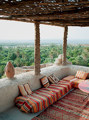 The terrace of a small hotel in Dades, overlooking the palms of the Skoura Oasis in Morocco - p429m802709 by Cultura