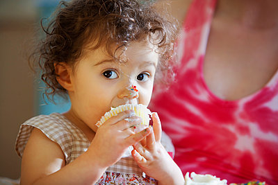 Messy baby girl eating cupcake - p555m1311407 by Shestock