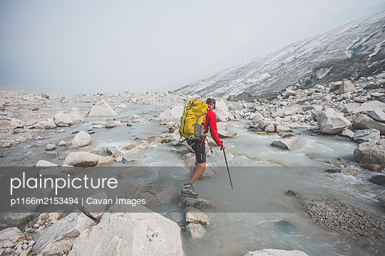 Backpacker uses large boulders to cross river next to glacier. - p1166m2153494 by Cavan Images