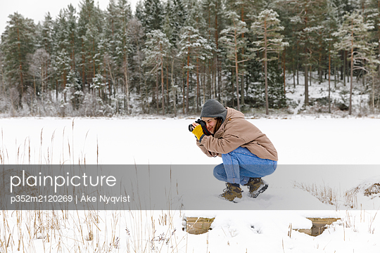 Crouching woman taking photograph on snow - p352m2120269 by Åke Nyqvist