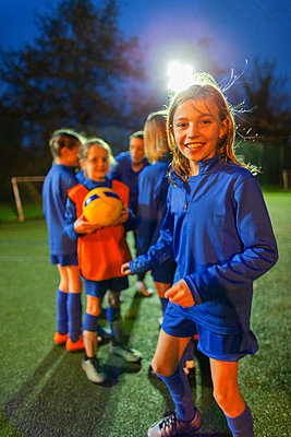 Portrait smiling, confident girl soccer player practicing with team on field at night - p1023m2035171 by Paul Bradbury