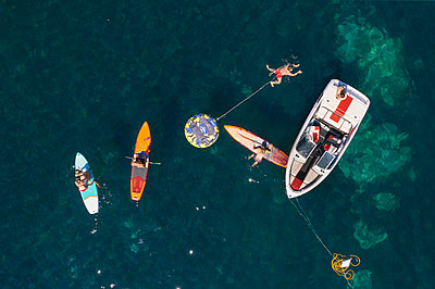 Driving a motorboat and stand up paddling - p1437m2283294 by Achim Bunz