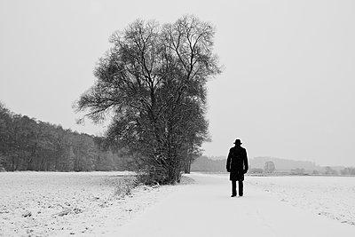 Mann in dunkler Kleidung in einer ländlichen Schneelandschaft - p1574m2147970 von manuela deigert