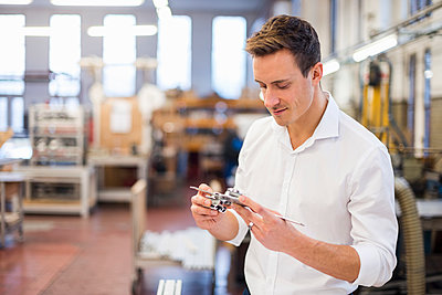 Young businessman in factory holding component - p300m1562793 by Daniel Ingold
