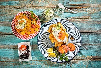 Baked Potato, sweet potato, Argentine red shrimp, sour cream on plate - p300m1588119 von Roman Märzinger