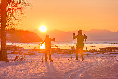 Two back lit people cross country skiing on the Tony Knowles Coastal Trail at sunset, Southcentral Alaska - p442m1033950 by Design Pics