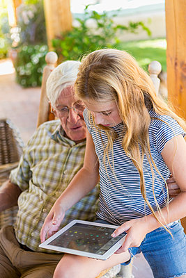 Caucasian grandfather and granddaughter using digital tablet - p555m1410674 by Marc Romanelli