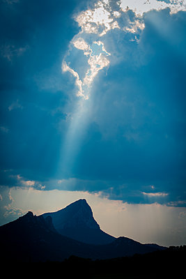 Sunbeams shed light on mountain peak - p829m1110851 by Régis Domergue