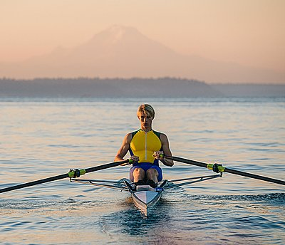 Teenage boy in sculling boat on water - p924m1108037f by Pete Saloutos
