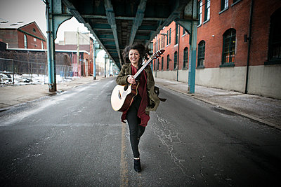 Young woman running below elevated road with acoustic guitar - p924m1230128 by Zave Smith