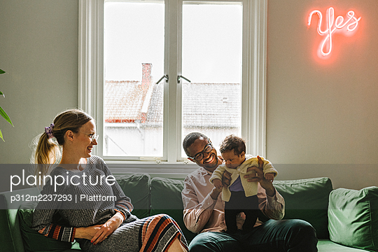 Parents with baby girl sitting on sofa - p312m2237293 by Plattform