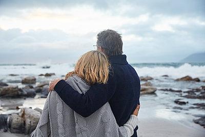 Serene couple hugging on winter beach - p1023m1217902 by Ryan Lees