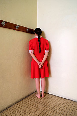 Woman in red dress standing in the corner - p1521m2081630 by Charlotte Zobel
