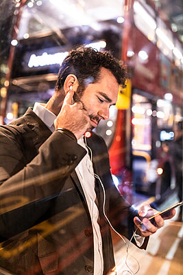 UK, London, businessman with cell phone and earbuds at the bus station by night - p300m2069714 by William Perugini