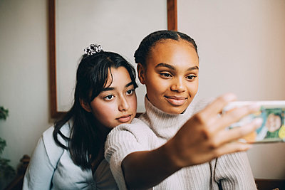 Teenage girls taking selfie with smartphone at home - p426m2145556 by Maskot
