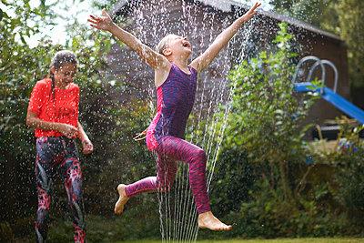 Girls jumping over garden sprinkler - p429m1494588 by Peter Muller