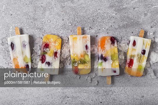 Homemade fruits and yogurt ice lollies on marble - p300m1581587 von Retales Botijero
