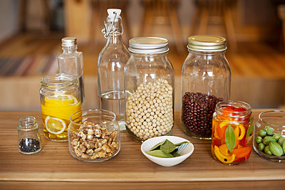 Close up of a selection of condiments and dried pulses in glass jars. - p1100m2146714 by Mint Images