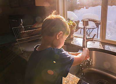 Boy washing hands at kitchen sink by window during winter - p1166m1567494 by Cavan Images