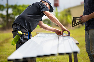 two men measure brackets for mounting solar panels. - p1166m2157136 by Cavan Images