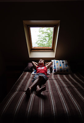 Young boy laying on bed looking up through a sky light in a dark room. - p1166m2207995 by Cavan Images