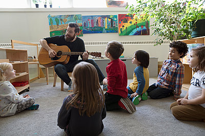Male teacher with guitar teaching preschool students in classroom - p1192m1560128 by Hero Images