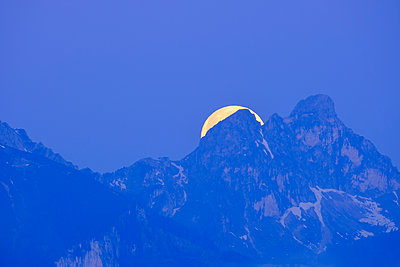 Germany, Bavaria, Moon hiding behind peaks of Tannheim Mountains at blue dawn - p300m2199496 by Martin Siepmann