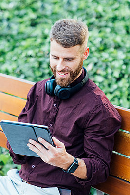 Smiling businessman with headphones using digital tablet while sitting on bench - p300m2250364 by Boy photography