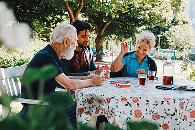 Cheerful senior woman playing cards with males at table in back yard - p426m2074375 by Maskot