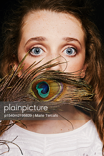 blurred portrait of a little girl with a peacock feather - p1540m2195839 by Marie Tercafs