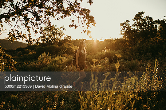 Woman looking away while standing in forest during sunset - p300m2213969 by David Molina Grande